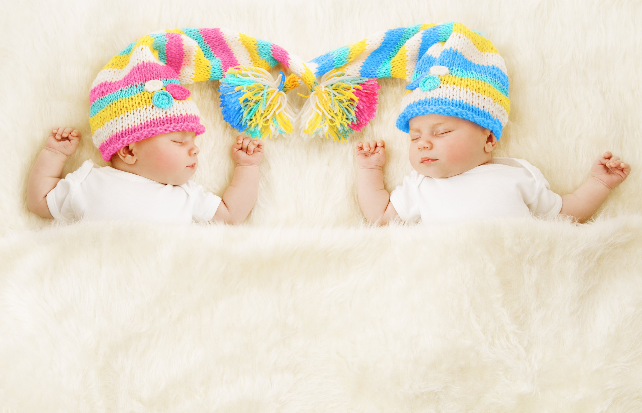 cute twin babies in knitted hats asleep