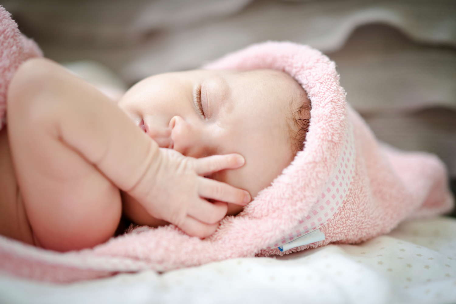 baby sleeping in pink hat