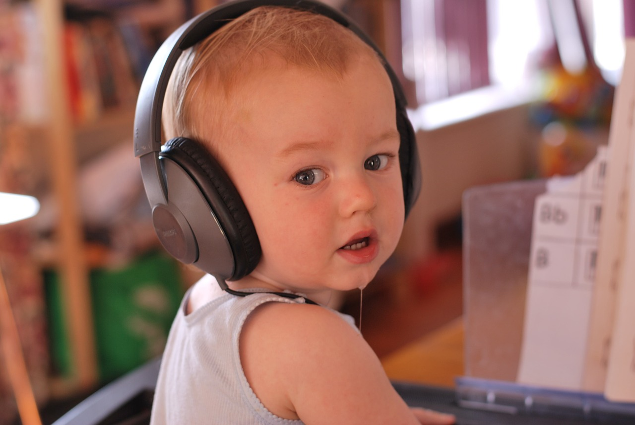 baby with headphones listening to music