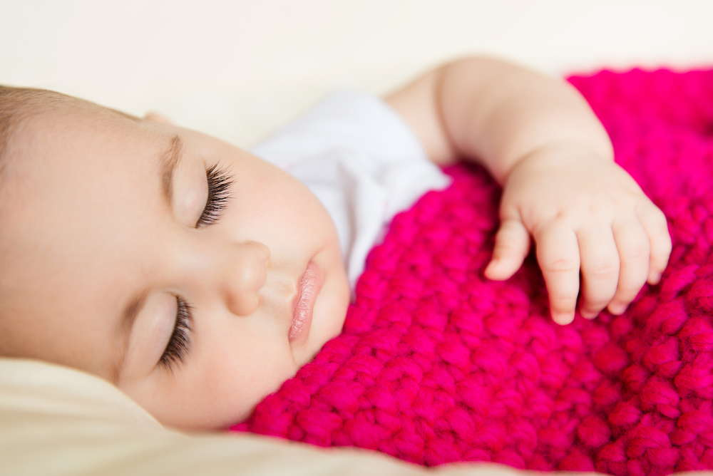 toddler asleep in a pink blanket
